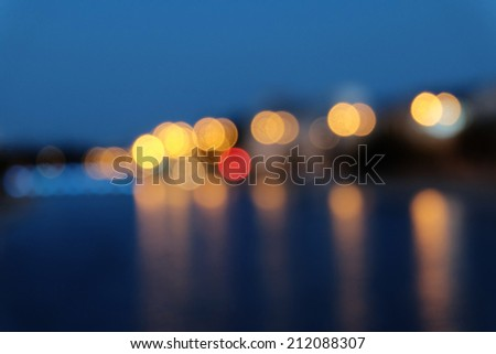 Blurred city lights with bokeh effect reflected on water surface - stock photo