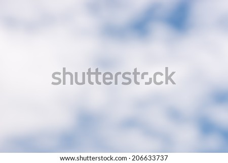 Blurred cloudscape background with soft white clouds in a blue sky conceptual of the weather, nature and the environment. - stock photo