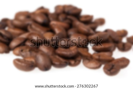 Blurred coffee grains on a white background. - stock photo