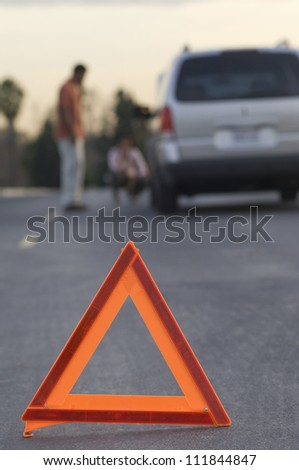 Blurred couple in discussion with warning triangle in foreground - stock photo