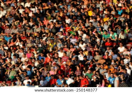 Blurred crowd of people at a football match in a stadium - stock photo
