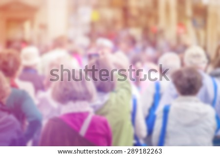 Blurred Crowd of Senior People On Street, Citizenship Concept with Unrecognizable Crowded Old Population out of Focus, Vintage Toned Image. - stock photo