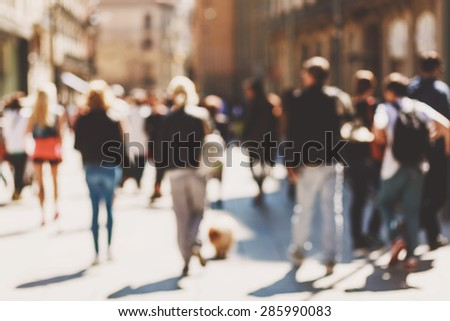 Blurred crowd of walking people in the city with buildings in the background - stock photo