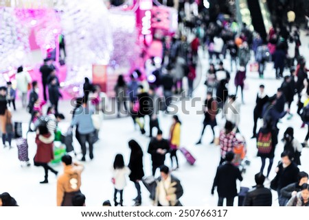 Blurred crowded people in shopping mall - stock photo