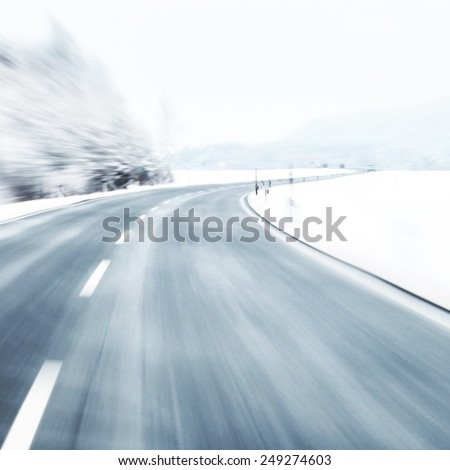 Blurred dangerous and fast turn at the icy snow road. Motion blur visualizies the speed and dynamics. - stock photo