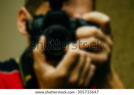 Blurred defocused photo of the cameraman with camera in hand, for background and other design - stock photo