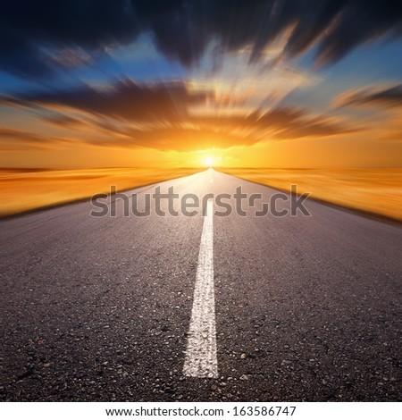 Blurred empty asphalt road at sunset - stock photo