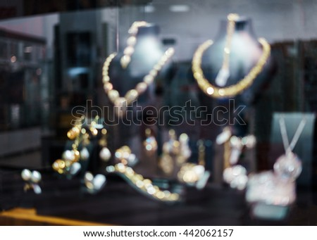 Blurred fashion boutique with jewelry made of precious metals. Store jewelry in silver and gold. Vetrin beautiful jewelry store. Blurred bokeh basic background for design - stock photo