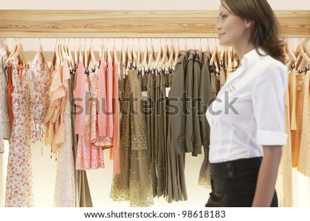 Blurred figure of a sophisticated store assistant walking through a fashion store. - stock photo