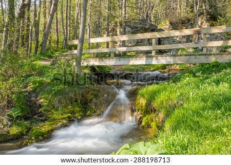 Blurred flowing stream & waterfall under wooden bridge at Big Hill Springs Provincial Park in Alberta, Canada - stock photo