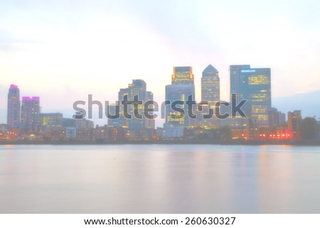 Blurred foggy Cityscape of London Canary Wharf business district overlooking the river Thames. - stock photo