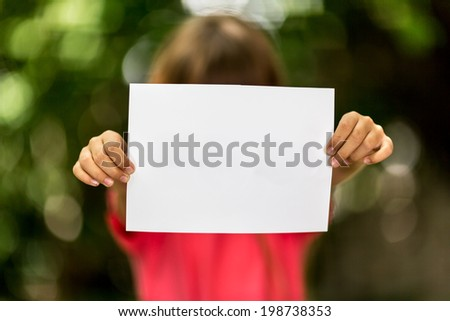 Blurred girl holding a blank piece of paper with copy space in front of her. - stock photo