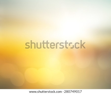 Blurred golden autumn, yellow, orange nature background. Sandy beach backdrop with turquoise water and bright sun light. Summer holidays concept. - stock photo