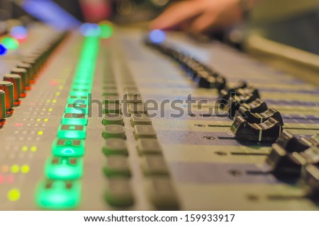 Blurred Hand on a mixer, operating the leader. Night concert scene. Wide angle, shallow deepth of field - stock photo