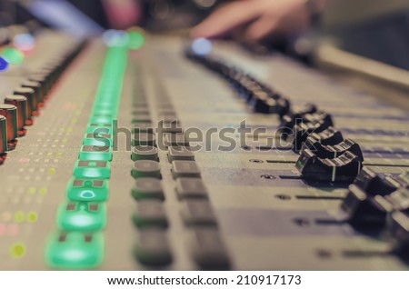 Blurred Hand on a mixer, operating the leader. Night concert scene. Wide angle, shallow deepth of field, VINTAGE - stock photo