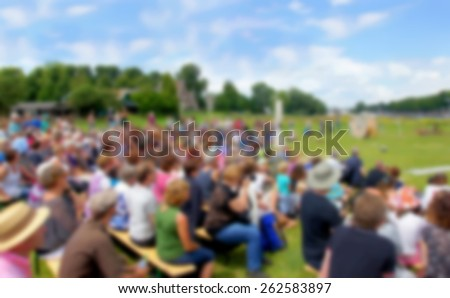 blurred image from a crowd / audience of people standing outside  - stock photo