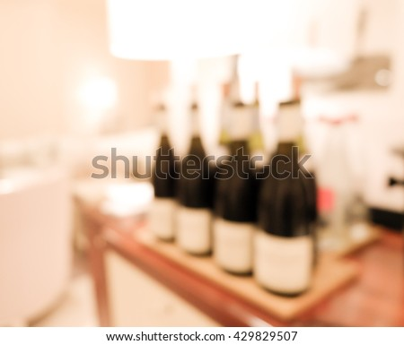 Blurred image of bottles of wine - stock photo