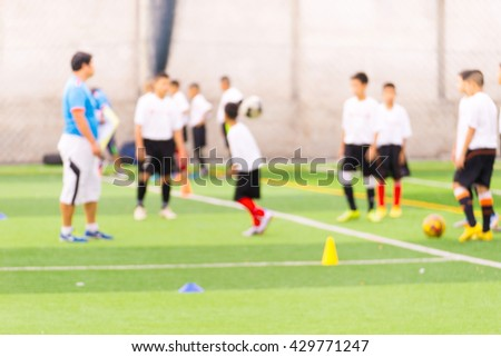 Blurred image of Children Training In Soccer Team - stock photo