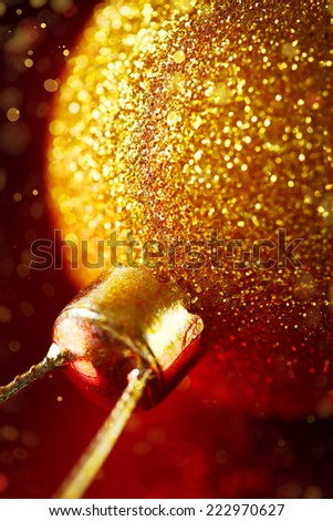 Blurred image of Christmas decoration with gold baubles and glitter on red background. Xmas and new year greeting. Close up, selective focus. - stock photo