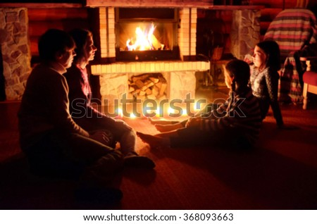 Blurred image of family sitting near fireplace in house, parents and kids relaxing and having fun near fire  - stock photo