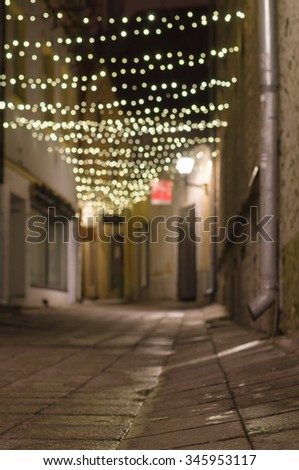 Blurred image of narrow city street decorated with illuminated festoon - stock photo