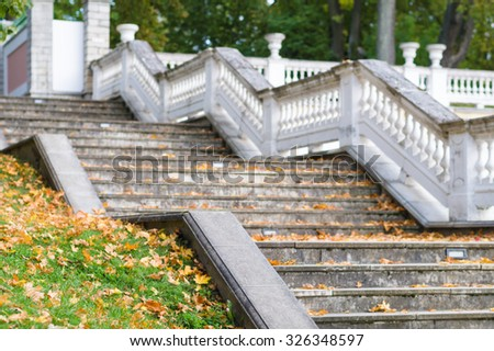 Blurred image of outdoor old style staircase with decor railing and fall leaf - stock photo