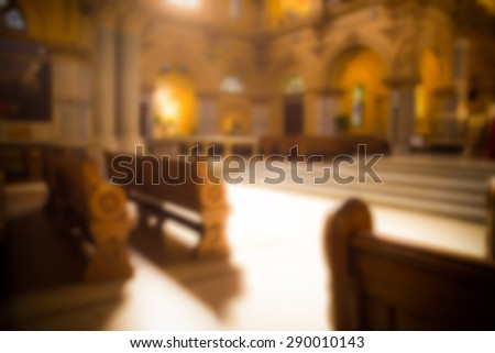 blurred image of pews and alter in typical Catholic church - stock photo