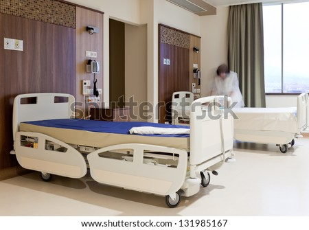 Blurred image of staff member in medical uniform fixing hospital bed - stock photo