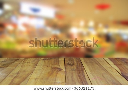 blurred image wood table and abstract shopping mall, bokeh background - stock photo