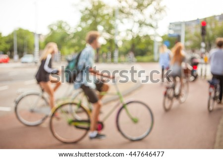 Blurred image young city cyclists crossing the crossroad of modern city. Ecological means of traveling. - stock photo