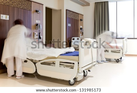 Blurred images of staff members changing hospital bed sheets in modern equipped room - stock photo