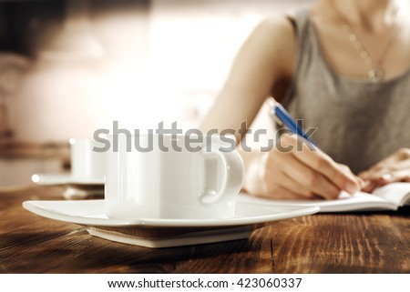 blurred interior of retro kitchen and blue pen woman and coffee  - stock photo