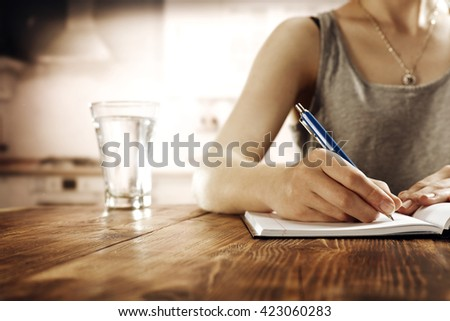 blurred interior of retro kitchen and single water glass and blue pen  - stock photo