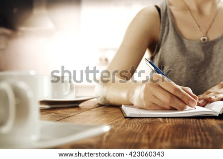 blurred interior of retro kitchen and woman hands and blue pen  - stock photo