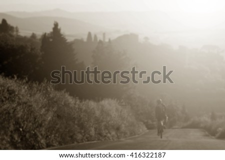 Blurred landscape three Cycling riding bicycle on country road near pienza tuscany italy and Cross process with soft flare filter - stock photo