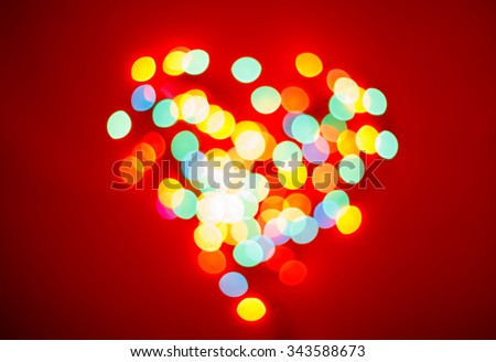 Blurred lights in a shape of a heart on red valentine background - stock photo