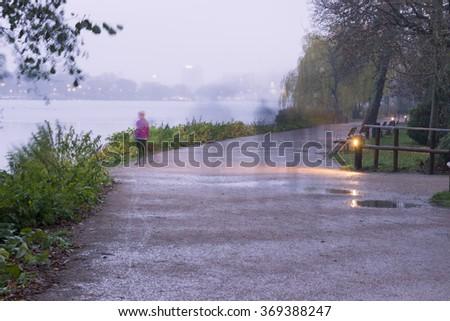 Blurred, long exposure shot of river/sea/lake, pedestrians walking. Hamburg, Germany. - stock photo