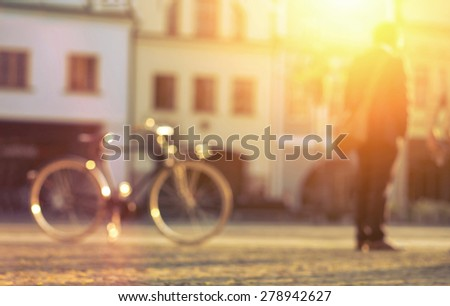 Blurred man with bicicle stay on the street at sunny day. - stock photo