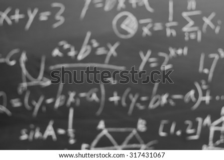 Blurred maths formulas written by white chalk on the blackboard background. - stock photo