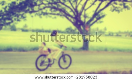 blurred mother and son riding bicycle, vintage filter - stock photo