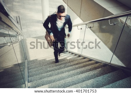 Blurred motion of businessman going upstairs in office building - stock photo