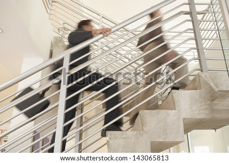 Blurred motion of businessmen moving upstairs in office - stock photo