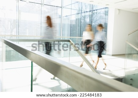 Blurred motion of businesswomen walking at office hallway - stock photo