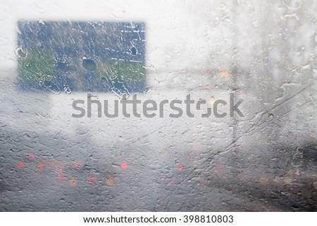 Blurred motion of dense traffic on road during hard rainy day with rain drops splashing windscreen  - stock photo