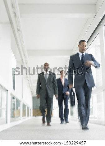Blurred motion of multiethnic businesspeople walking in office corridor - stock photo
