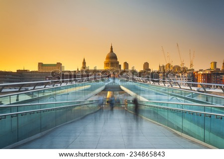 Blurred motion view over the Millennium footbridge looking towards St. Paul's Cathedral at sunset - stock photo