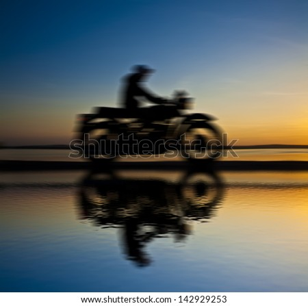 blurred motorcyclist against blue sunset with reflection on water - stock photo