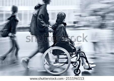 blurred movement disabled on a city street and blue tonality - stock photo