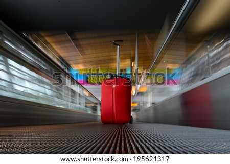 blurred moving escalator with red trolley in airport - stock photo