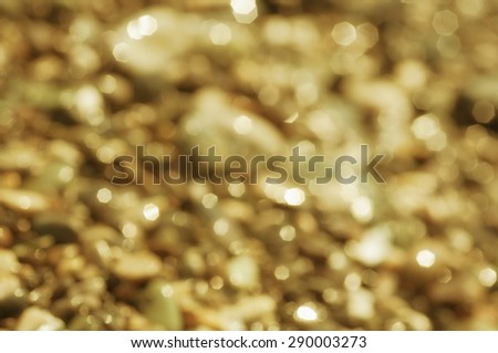 Blurred natural seasonal  background with golden sea pebble  - stock photo